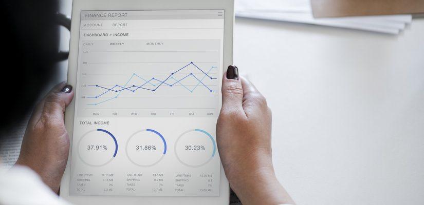 femme regardant une tablette avec des statistiques affichées