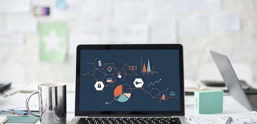 ordinateur portable posé sur un bureau avec des graphiques à l'écran