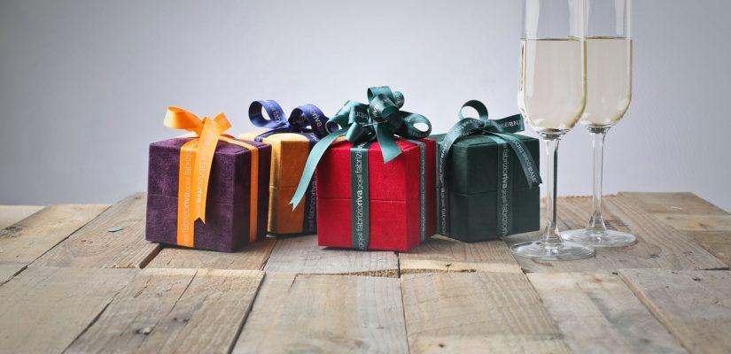 petits cadeaux emballés posés à côté de deux flûtes de champagne
