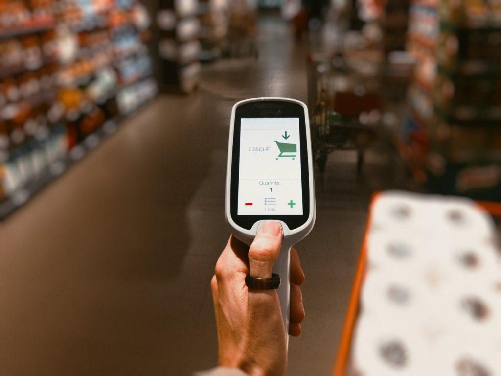 personne tenant une scanette de produits dans un supermarché